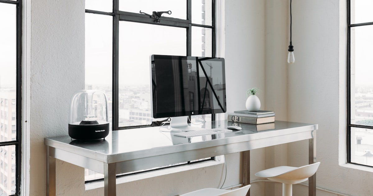Modern desk clear except for streamlined computer sitting against industrial window.
